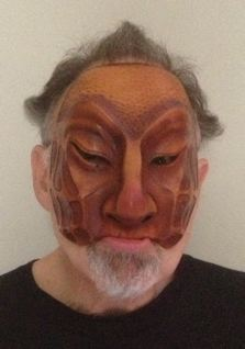 Newman modelling a handcrafted leather Dell'Arte mask: Zanni
